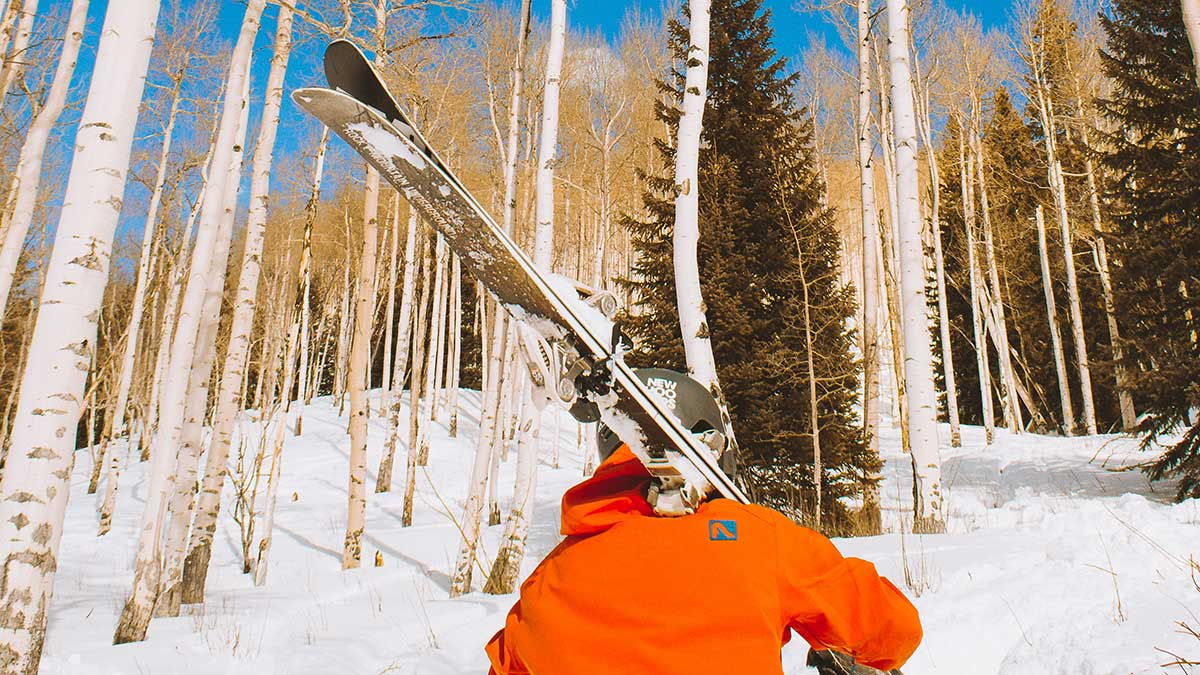 Skier walking through the forested mountains of Vail, Colorado
